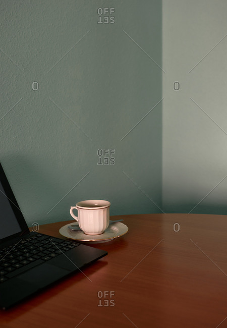 Coffee cup and a tablet on a corner table. Conceptual image
