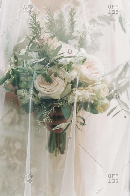 Bride keeping her wedding bouquet under her veil