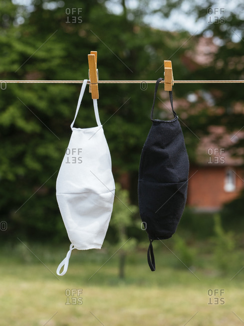 Two washable community face masks hanging on a clothes line