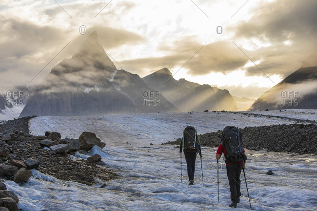 Backpackers on the move hiking toward iconic Mount Loki, Baffin Island