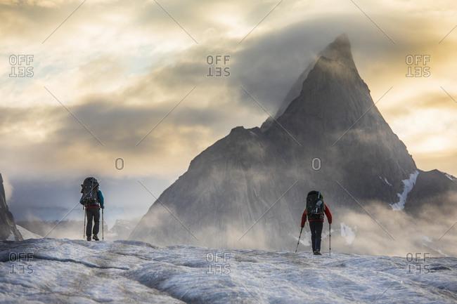 Two backpackers hiking towards Mt. Loki, Baffin Island, Canada.