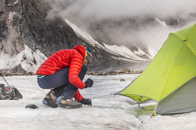 Mountaineer staking tent on glacier in Akshayak Pass.