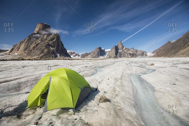 Green tent on glacier in mountain landscape, Baffin Island