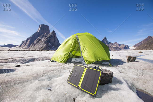 Solar panel charger with tent in background at remote campsite