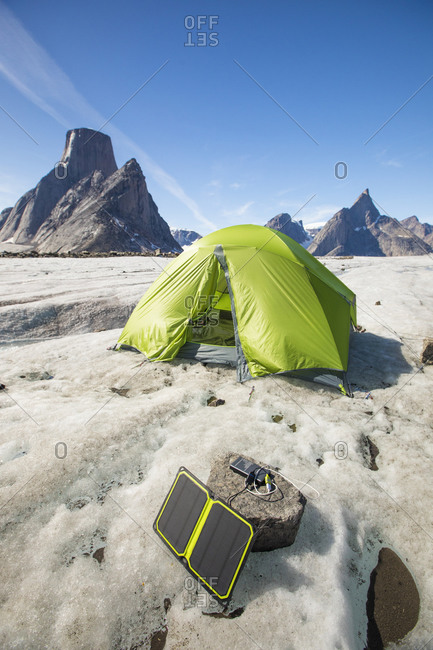 Solar panel charging with tent in background at remote campsite