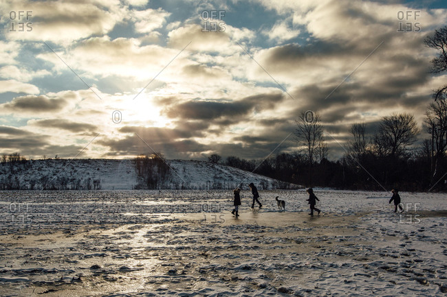 Children playing on ice in field with morning sun