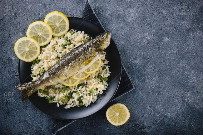 Delicious roasted trout seasoned with spices and lemon juice with rice