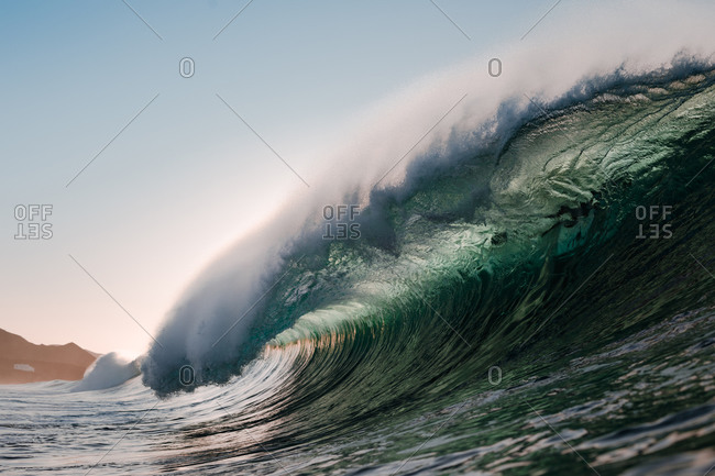 Wave breaking under the sunset on the beach