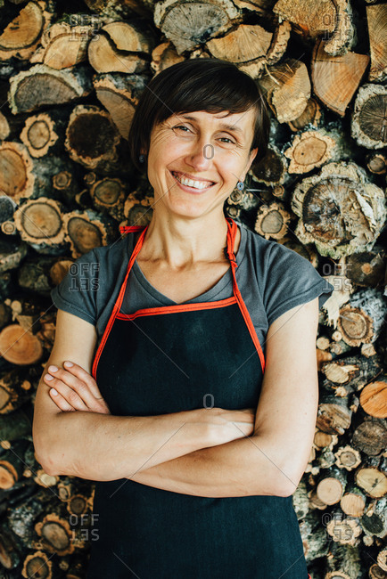 Portrait of female woodworker looking at camera and smiling, close up