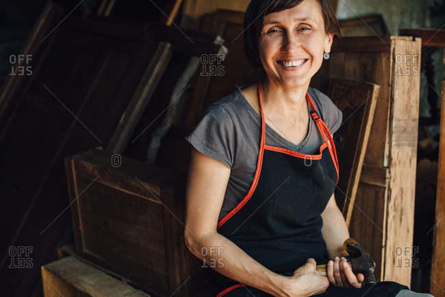 Happy female carpenter with hammer in workshop smiling at camera