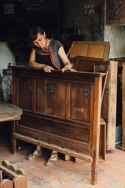 Female restorer working with ancient wooden furniture in workshop