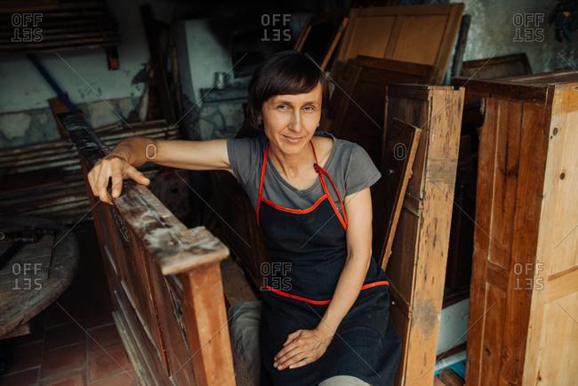 Female carpenter resting in workshop looking at camera