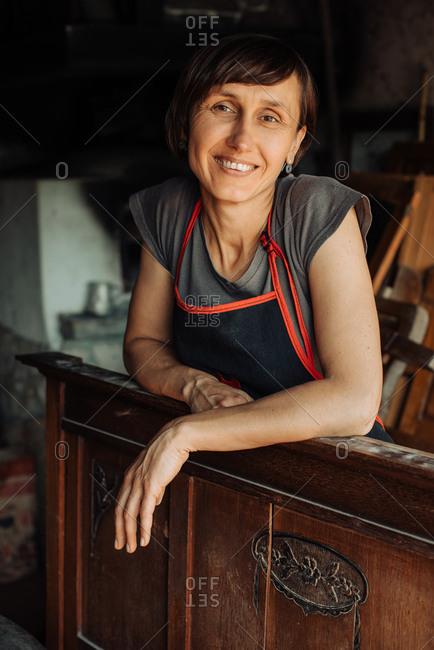 Professional female restorer or carpenter looking at camera, smiling
