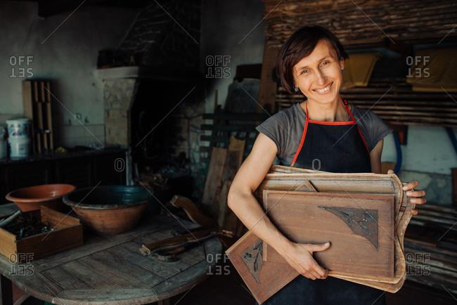 Smiling female craftsperson holding wooden panels in workshop