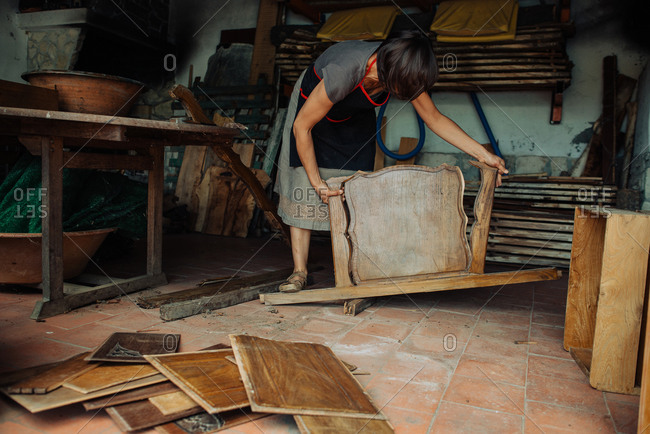 Female artisan working reusing old wooden furniture for artistic use