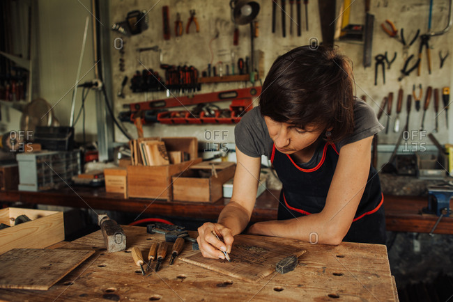 Female woodworker working at the workbench in a workshop