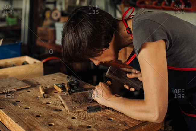 Woman working at workbench, using hand tools