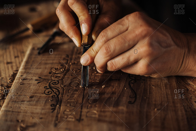 Close up process of decorative wood engraving using hand tools