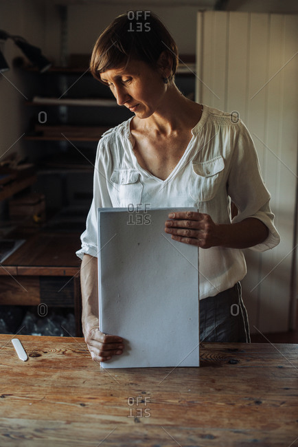 Woman handling stack of paper sheets, handmade book production process