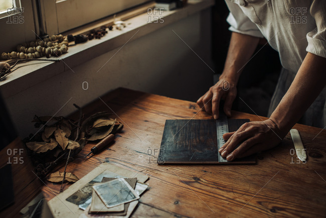 Hands of a craftswoman measuring object on the wooden surface