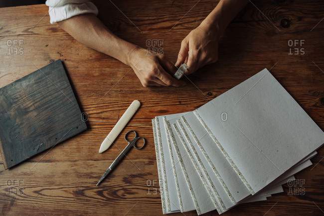 Hands, sheets of paper, wooden panel, scissors on wooden surface