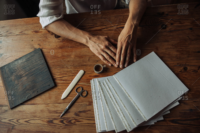 Hands of artist, paper sheets, scissors on a wooden table, top view