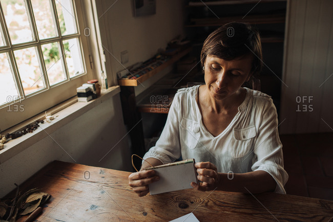 Female artisan sitting at table and stitching sheets of paper