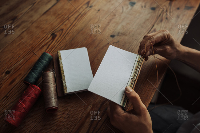 Hands stitching paper sheets in a book, top view