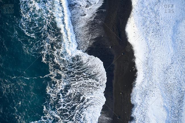Breaking waves rolling on seashore in winter