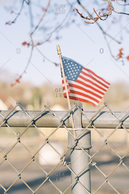 A weathered American flag on a chain-link fence during covid-19