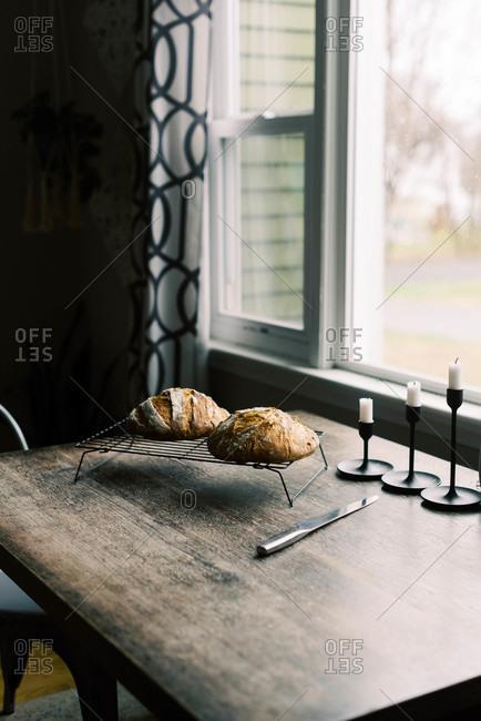 Fresh homemade sourdough bread on a cooling rack.