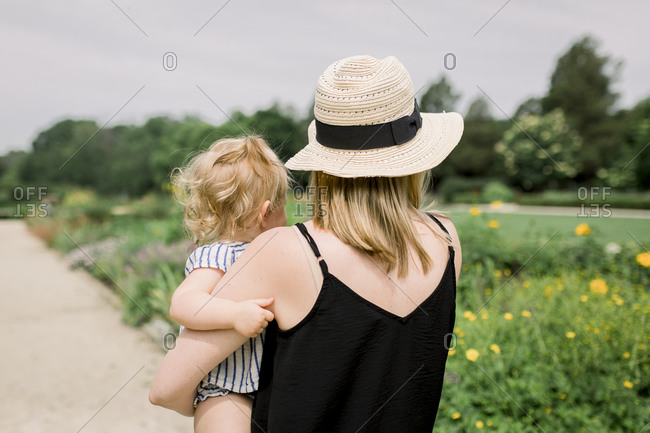 Mom with sun hat holding toddler while looking at a flower field