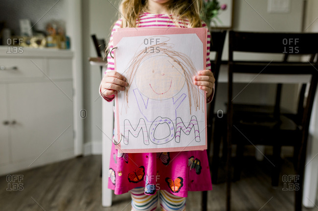 Young girl holding a drawing she made of her mom for Mother's Day