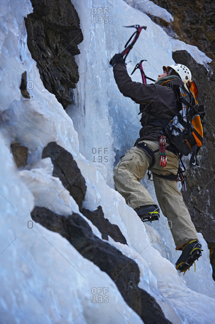 young man climbing frozen waterfall in Iceland
