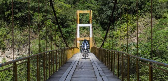Man driving touring motorbike on suspension bridge in Peru
