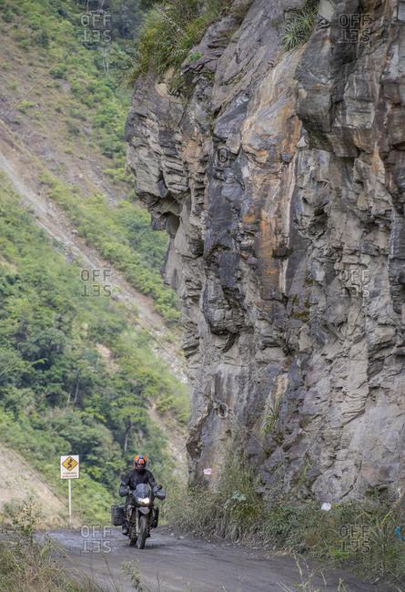 Man driving touring motorbike on dirt road, Santa Teresa, Piura, Peru