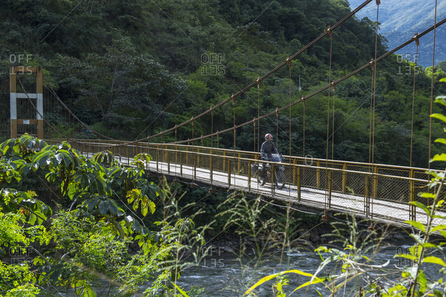 Man driving touring motorbike on suspension bridge