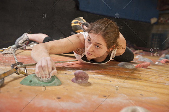 young woman practicing at indoor climbing wall in the UK