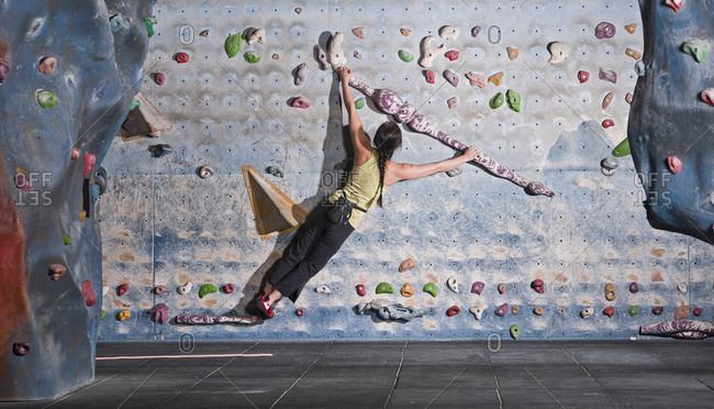 Mature woman practicing at indoor climbing wall in the UK