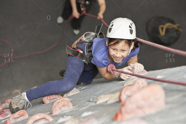 Young girl climbing at indoor climbing wall in England / UK