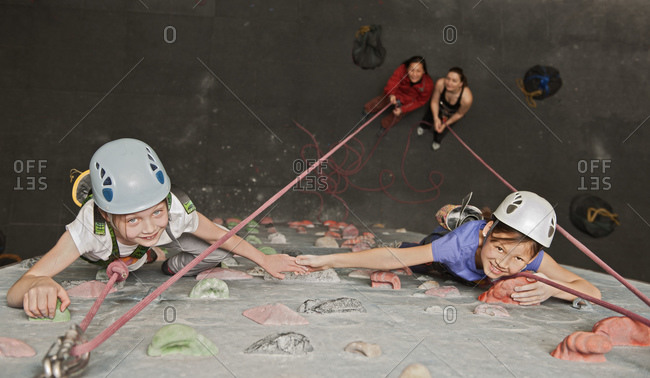 Two young girls climbing at indoor climbing wall in England / UK