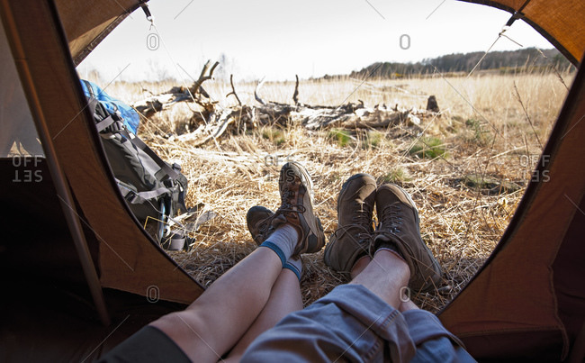 couple lying inside a tent with their feet outside
