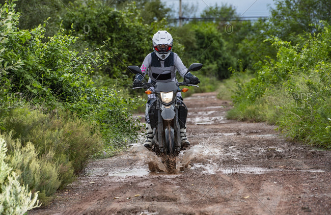 Woman driving her motorbike on dirt road in Thailand