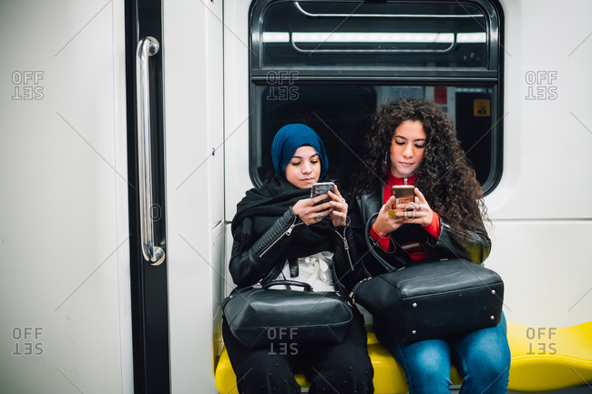 Young woman in hijab and friend sitting on subway train looking at smartphones