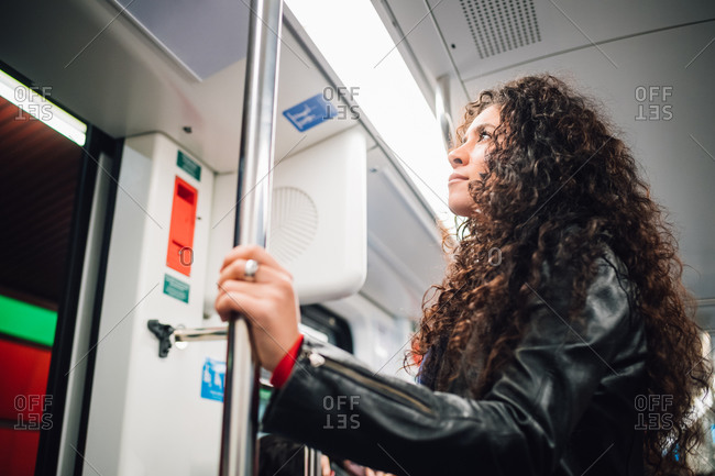Mid adult woman with long curly hair on city subway train