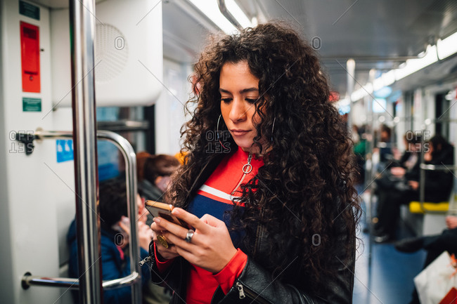 Mid adult woman with long curly hair looking at smartphone on city subway train