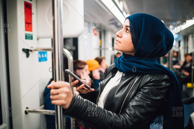 Young woman in hijab with smartphone on subway train