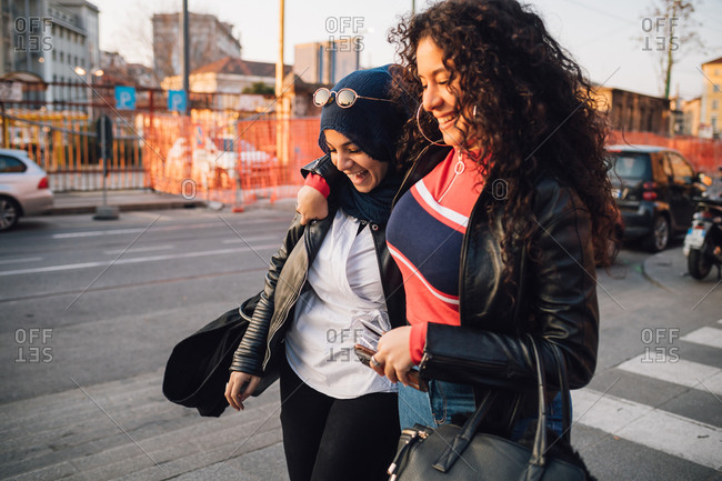 Young woman in hijab and best friend walking and talking in city