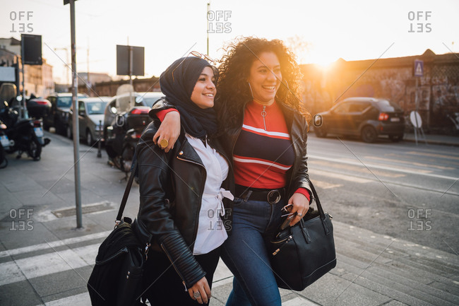 Young woman in hijab and best friend walking and talking in city at sunset
