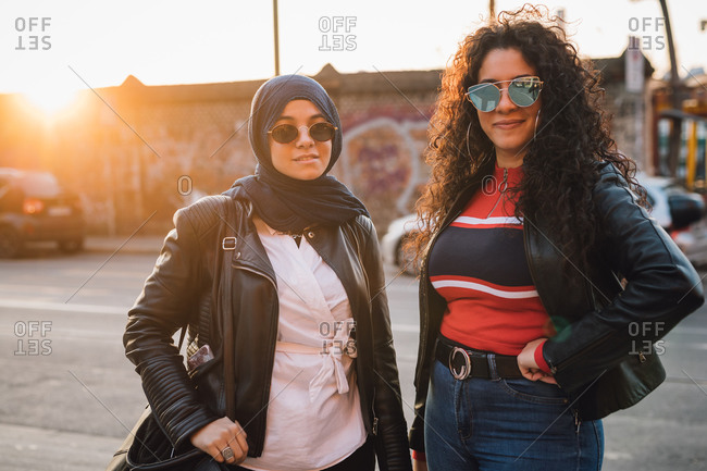 Young woman in hijab and best friend in city at sunset, portrait